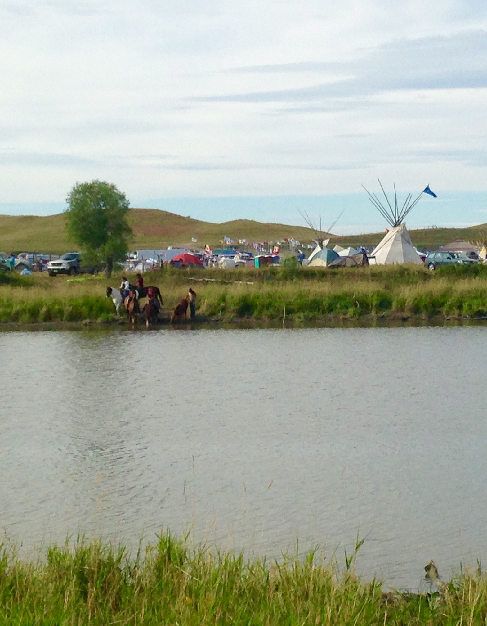 Lakota Sioux and horses drinking at the edge of the Missouri River by the Council Tipis.